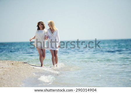 happy girls in white dresses  running on the sea beach
