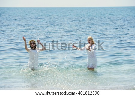 happy girls in white dresses splashing in the sea