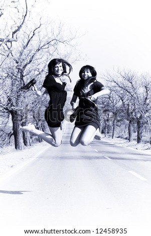 Happy girls jumping in the middle of the road