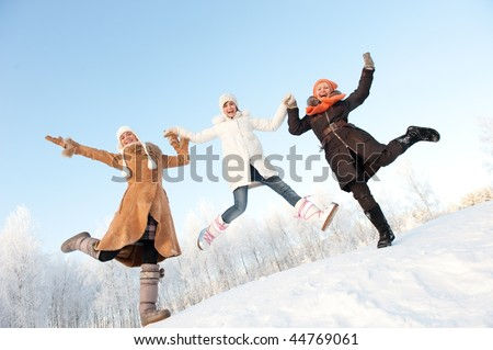 Happy girls jumping in the snow - stock photo