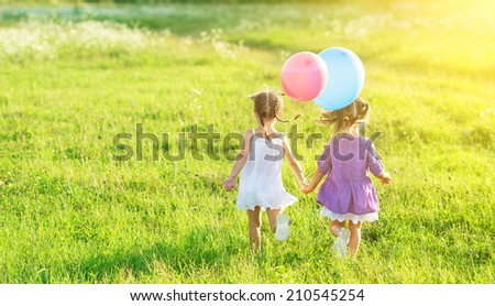 happy girls kids twin sisters with balloons in summer field on nature - stock photo