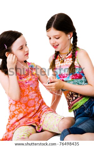 Happy girls listening to MP3 player isolated over white - stock photo
