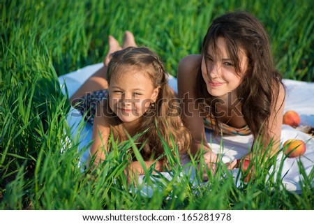 Happy girls on green grass at spring or summer park picnic
