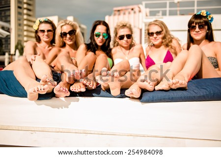 happy girls on the beach. beautiful girlfriends lying on a lounger by the pool and show their legs.  - stock photo