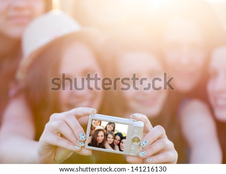 Happy girls outdoors photographing in difficult conditions taking self- portrait of themselves - selfpic series. - stock photo