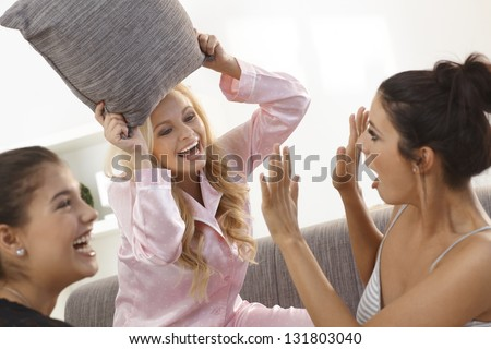 Happy girls pillow fighting in pyjamas, having fun. - stock photo