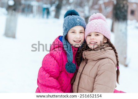 Happy girls playing on snow in winter time - stock photo