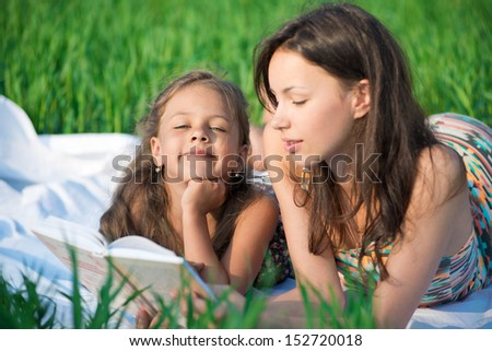 Happy girls reading book on green grass at spring or summer park picnic