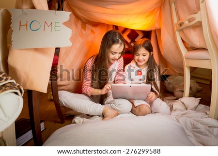 Happy girls sitting in house made of blankets and using digital tablet - stock photo