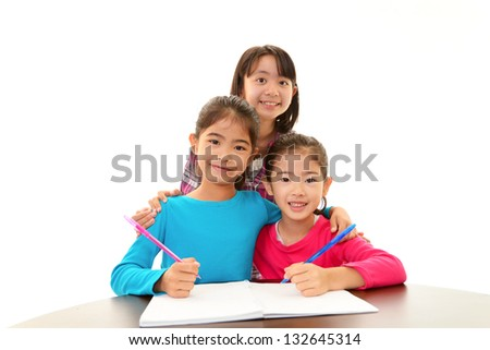 Happy girls studying at the desk - stock photo
