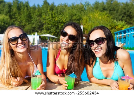 Happy girls with beverages on summer party in the pool - stock photo