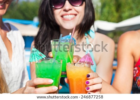 Happy girls with beverages on summer party making a toast near the pool  - stock photo