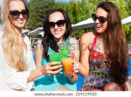 Happy girls with beverages on summer party near the pool