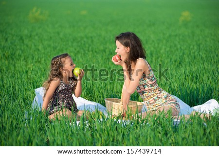 Happy girls with fruits on green grass at spring or summer park picnic