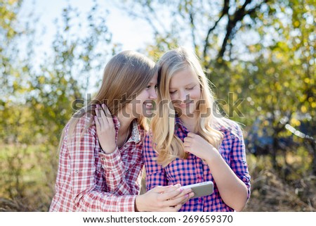 Happy girls with mobile phone outdoors - stock photo