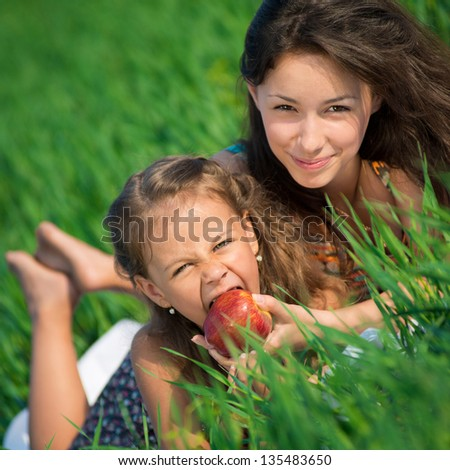 Happy girls with red apple on green grass at spring or summer park picnic - stock photo