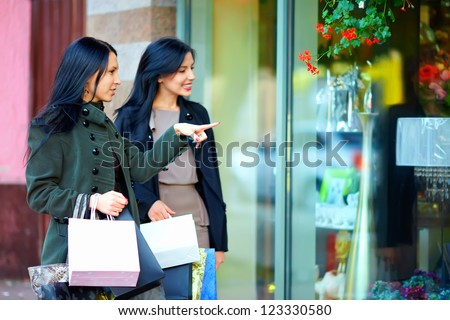 happy girls with shopping bags pointing finger in the shop window