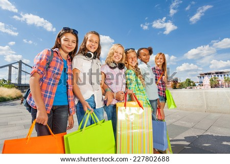 Happy girls with shopping bags stand together