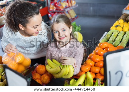 Happy glad mother and smiling little girl choosing fresh fruits in grocery