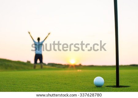Happy golf player on a golf court at a luxury resort, sunset shot - stock photo