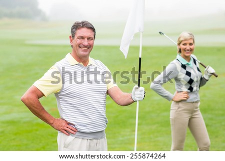 Happy golfer holding flag for cheering partner on a foggy day at the golf course - stock photo
