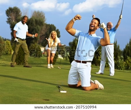 Happy golfer kneeling at hole with raised fists after putting in golf ball to the hole. - stock photo