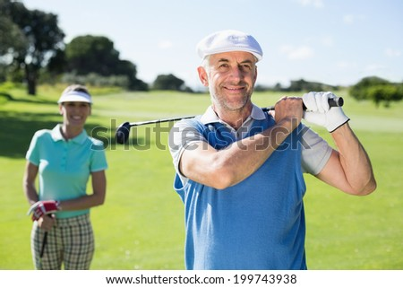 Happy golfer teeing off with partner behind him on a sunny day at the golf course - stock photo