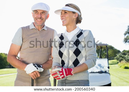 Happy golfing couple with golf buggy behind on a sunny day at the golf course - stock photo