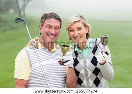 Happy golfing couple with trophy on a foggy day at the golf course - stock photo
