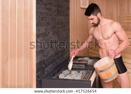 Happy Good Looking And Attractive Young Man With Muscular Body Pouring Water On Hot Rocks In Sauna - stock photo