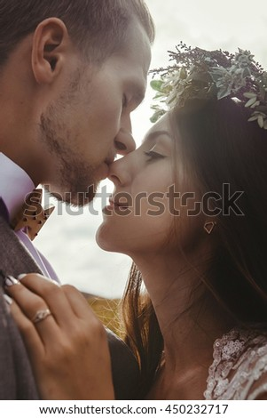 happy gorgeous bride and groom kissing in sun light, sensual perfect moment, boho wedding couple, luxury ceremony at mountains