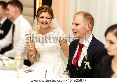 happy gorgeous bride and stylish groom cheering and toasting with guests and family at luxury wedding reception, emotional moment