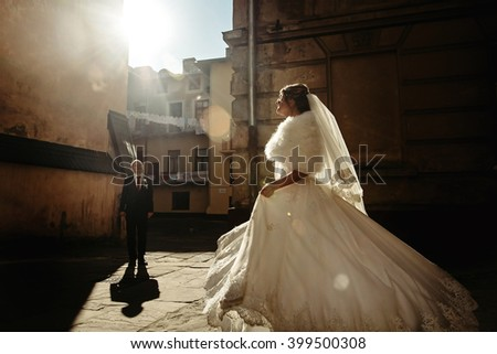 happy gorgeous bride and stylish handsome groom dancing on background of old buildings with amazing  view in sunlight patio