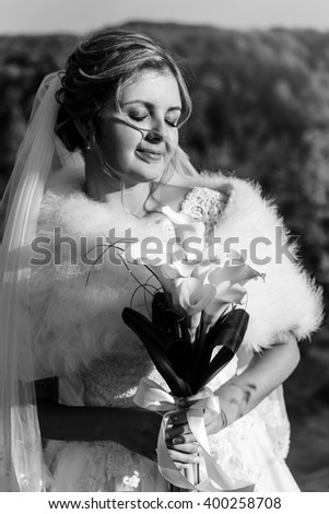 happy gorgeous bride posing and holding bouquet of callas on background of sunny trees forest, sweet romantic moment