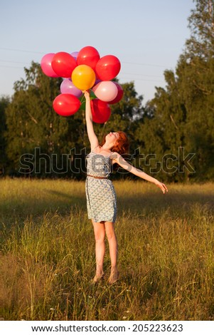 Happy graceful red haired teenager girl jumping flying with balloons outdoors