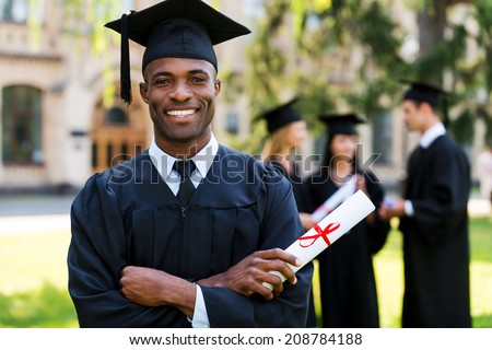 Happy graduate. Happy African man in graduation gowns holding diploma and smiling while his friends standing in the background  - stock photo