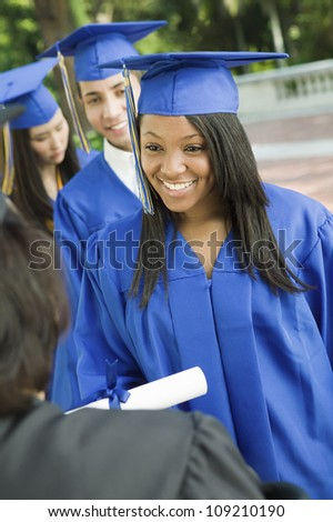 Happy graduates collecting certificate from female dean - stock photo