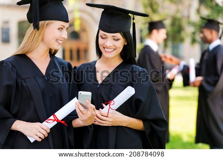 Happy graduates. Two happy women in graduation gowns looking at the mobile phone together and smiling while two men standing in the background  - stock photo
