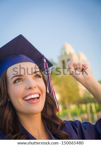 Happy Graduating Mixed Race Woman In Cap and Gown Celebrating on Campus. - stock photo