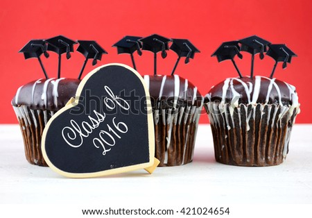 Happy Graduation Day party chocolate cupcakes with graduation cap hat topper decorations, in red and white party theme.  - stock photo