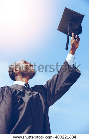 Happy graduation.. Low angle view of happy young African man in graduation gown holding his mortar board against blue sky - stock photo