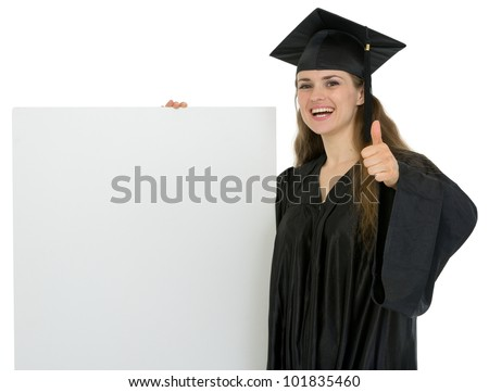 Happy graduation student girl holding blank billboard and showing thumbs up