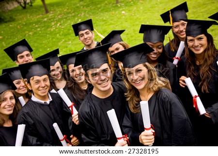 happy graduation students with diplomas outdoors - stock photo