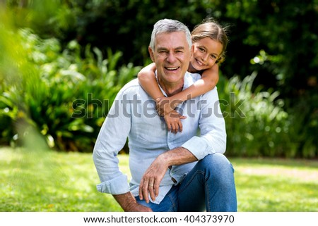 Happy grandfather and grandaughter smiling at yard - stock photo