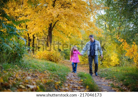 Happy grandfather and granddaughter in the autumn park