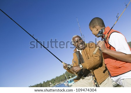 Happy grandfather and grandson fishing together on a sunny day - stock photo