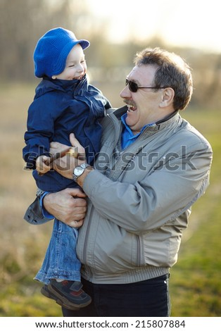 Happy grandfather and grandson having fun in autumn park
