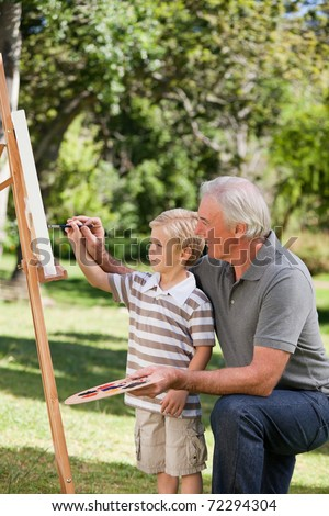 Happy Grandfather and his grandson painting in the garden - stock photo