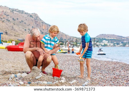 Happy grandfather and two little kid boys playing together on beach and building sand and stone castle. Beautiful family enjoying vacations on sea and ocean