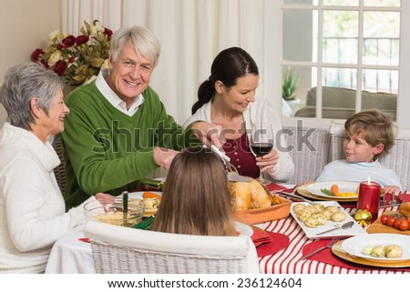 Happy grandfather carving chicken during christmas dinner at home in the living room